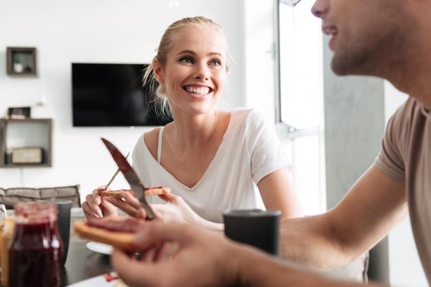 Donna felice che esamina il suo uomo mentre mangiano prima colazione