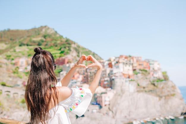 Donna felice che fa con le mani a forma di cuore sul vecchio villaggio costiero nel parco nazionale delle cinque terre.