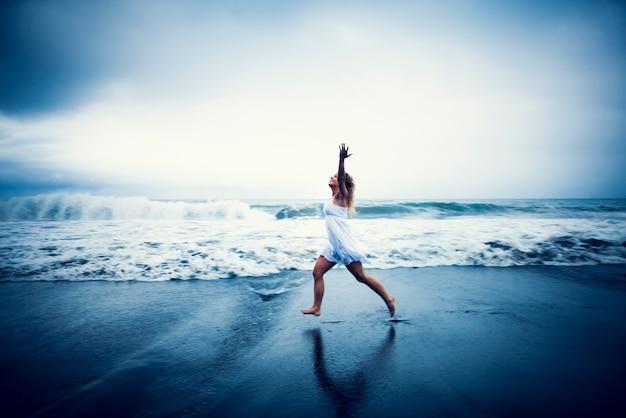 Donna felice che funziona sulla spiaggia