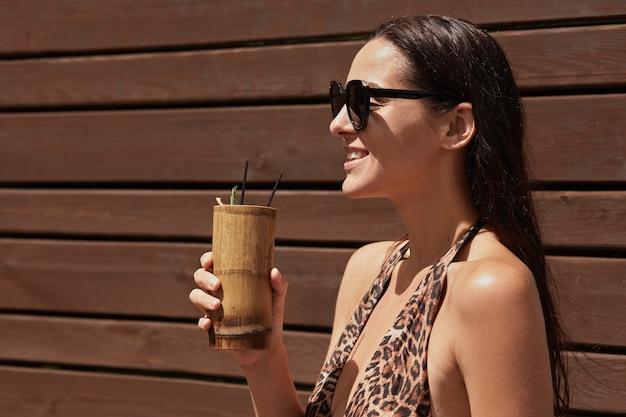 Donna felice che gode della bevanda esotica nel bar, guardando sorridente in lontananza, indossando occhiali da sole neri e costume da bagno