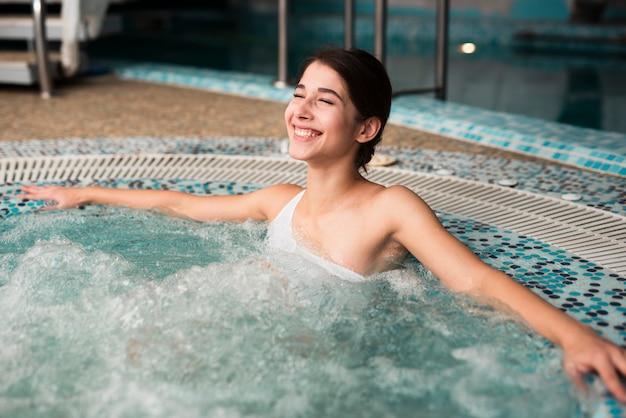 Donna felice che gode della stazione termale in vasca calda