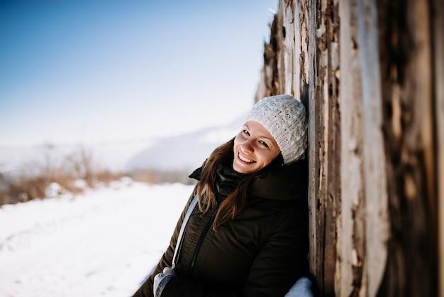Donna felice che gode su una montagna innevata. appoggiata al vecchio muro di legno.