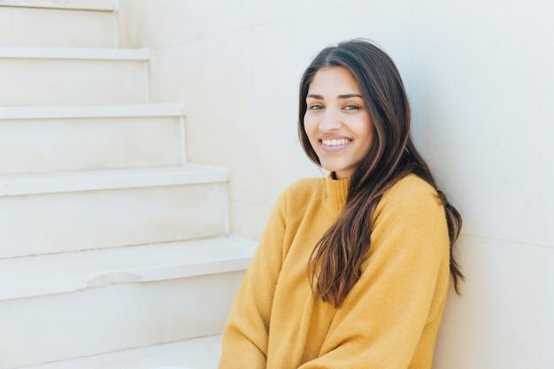 Donna felice che guarda l'obbiettivo che si siede sulla scalinata