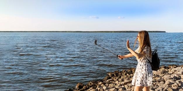 Donna felice che ha videochiamata utilizzando smartphone e monopiede sull'orizzonte del mare a sfondo tramonto