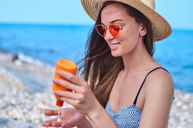 Donna felice che indossa il costume da bagno, cappello di paglia e occhiali da sole rosso brillante con la bottiglia di crema solare durante il sole al mare in tempo caldo e soleggiato in estate