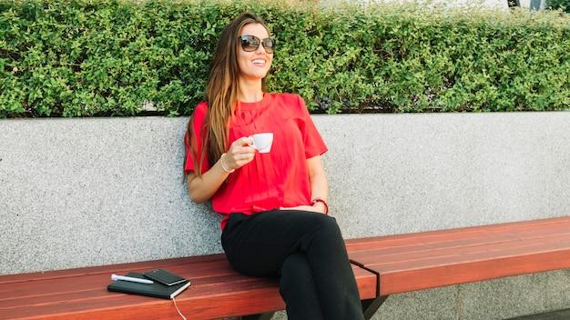 Donna felice che indossa occhiali da sole bevendo caffè