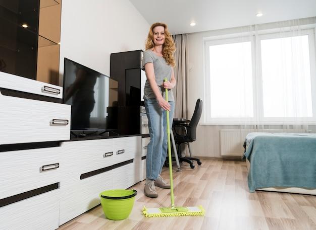 Donna felice che lava i pavimenti