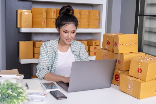 Donna felice che lavora con l'ufficio della cassetta dei pacchi del corriere e del computer portatile a casa ufficio