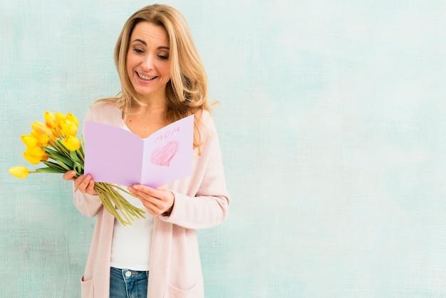 Donna felice che legge la cartolina del giorno del `s della madre