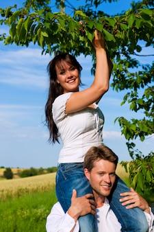 Donna felice che mangia le ciliege da un albero che si siede sulle spalle del suo uomo