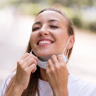 Donna felice che mette giù la sua mascherina medica
