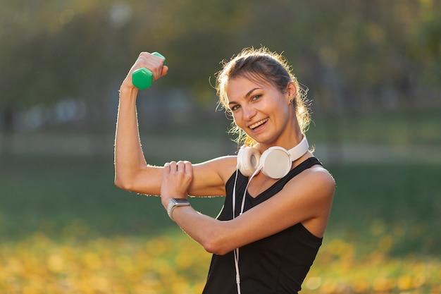 Donna felice che mostra i suoi muscoli