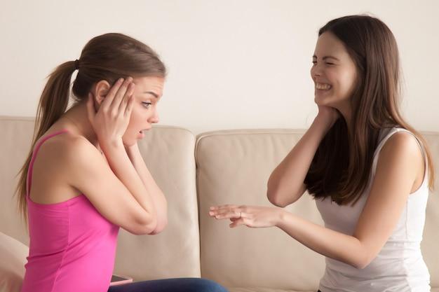 Donna felice che mostra il suo anello di fidanzamento all'amico