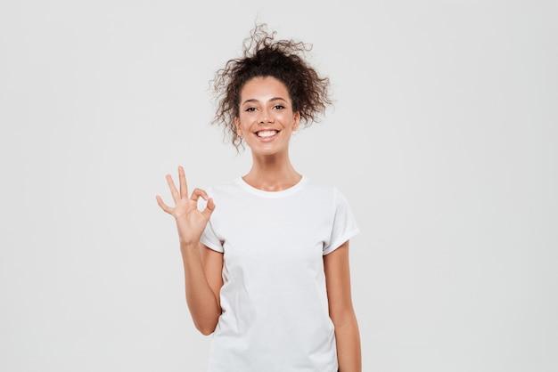 Donna felice che mostra segno giusto e che esamina la macchina fotografica