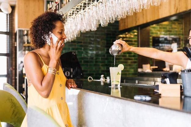 Donna felice che parla sul telefono cellulare che esamina barista che produce cocktail nella barra