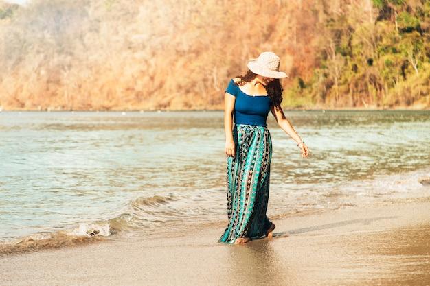 Donna felice che passeggia lungo il mare