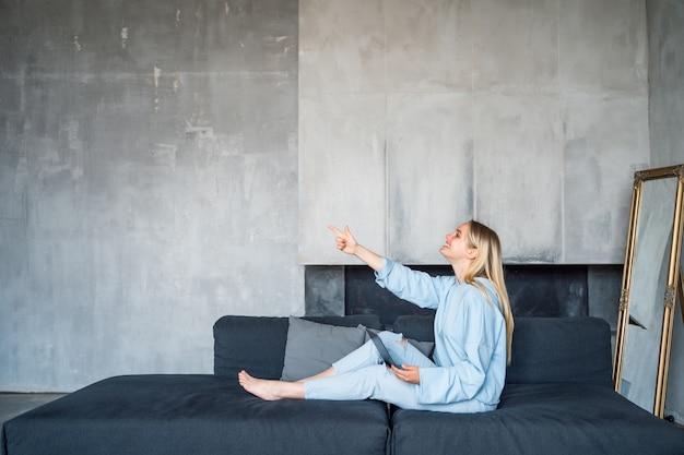 Donna felice che per mezzo del computer portatile d'argento mentre sedendosi sul sofà