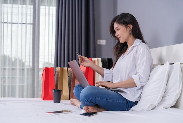Donna felice che per mezzo del computer portatile per acquisto online con la carta di credito sul letto