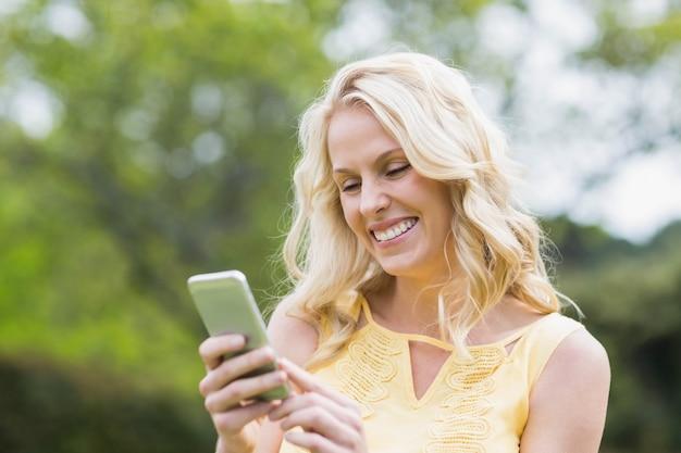 Donna felice che per mezzo dello smartphone fuori