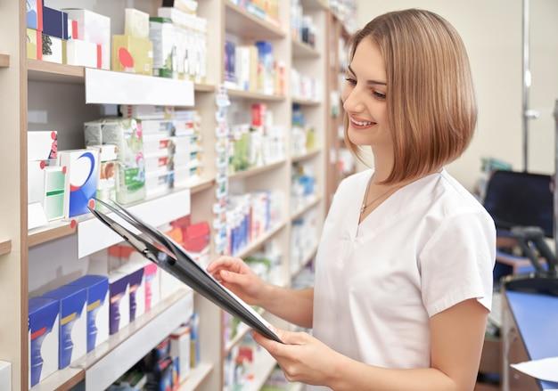 Donna felice che posa mentre si lavora in farmacia.