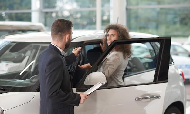 Donna felice che prende le chiavi oh nuova automobile dal responsabile.