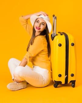 Donna felice che propone con i bagagli mentre porta il cappello