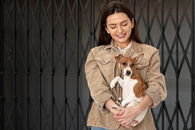 Donna felice che propone con il suo cane