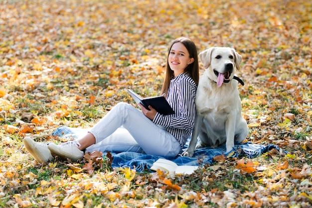 Donna felice che propone con il suo labrador