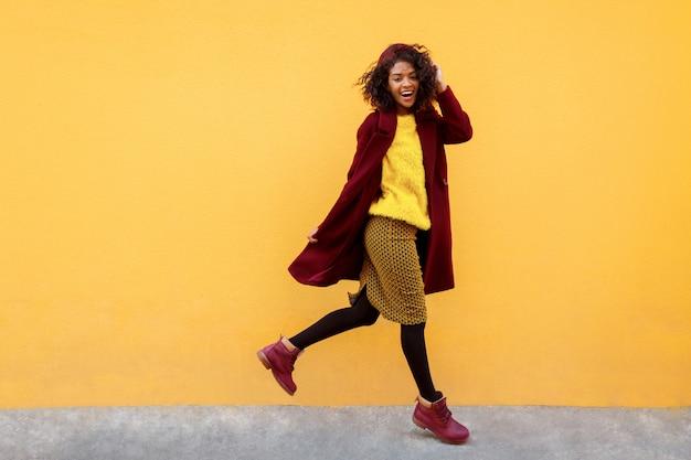 Donna felice che salta con l'espressione del viso felice sul giallo.