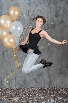 Donna felice che salta con palloncini