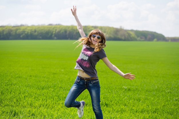 Donna felice che salta nel campo verde contro il cielo blu