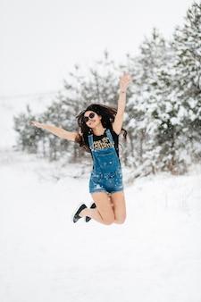 Donna felice che salta nella foresta di inverno