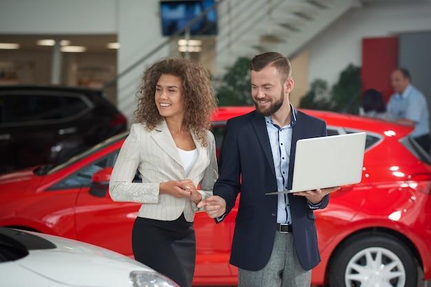 Donna felice che sceglie automobile con il gestore del concessionario auto.
