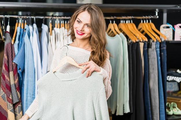 Donna felice che sceglie i vestiti nel negozio di abbigliamento