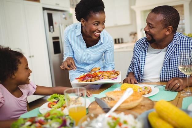 Donna felice che serve cibo per la famiglia