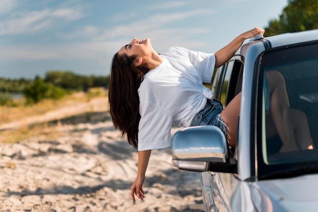 Donna felice che si appoggia sul finestrino della macchina