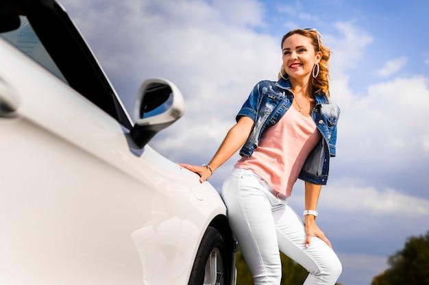 Donna felice che si appoggia sull'automobile