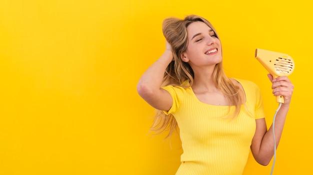 Donna felice che si asciuga i capelli