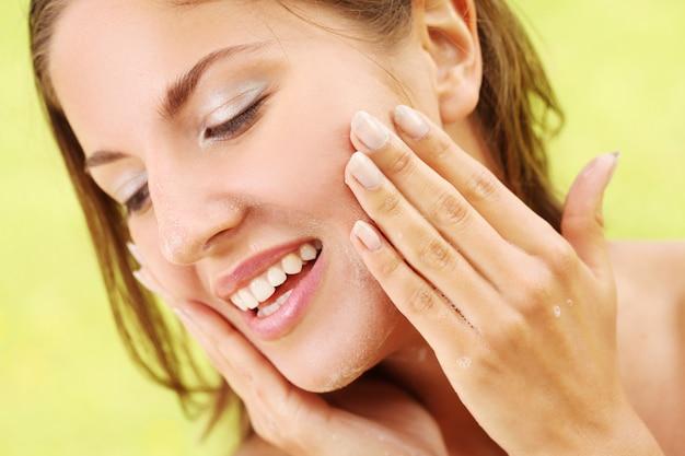Donna felice che si lava il viso