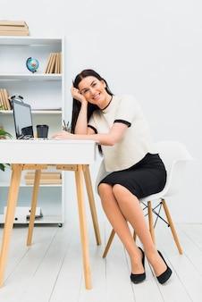 Donna felice che si siede al tavolo con il portatile