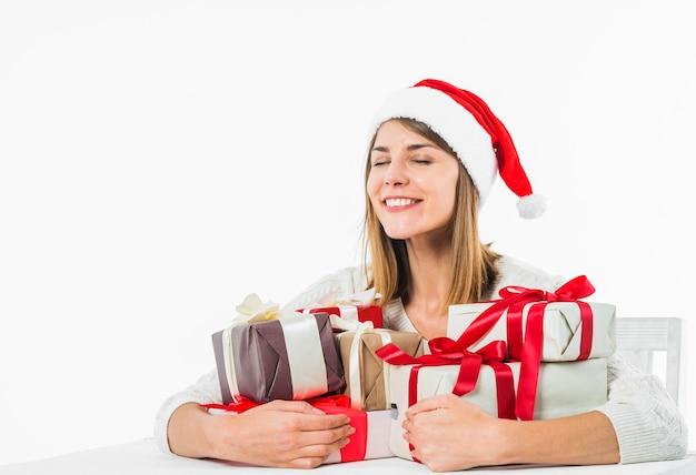Donna felice che si siede al tavolo con scatole regalo