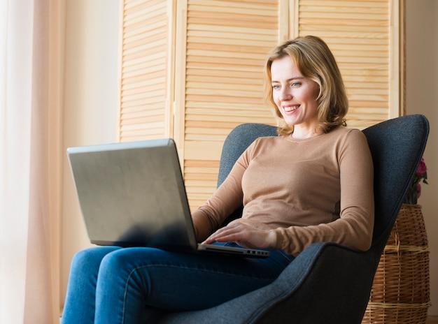 Donna felice che si siede e che utilizza computer portatile