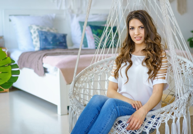 Donna felice che si siede in un'amaca lavorata a maglia nella stanza
