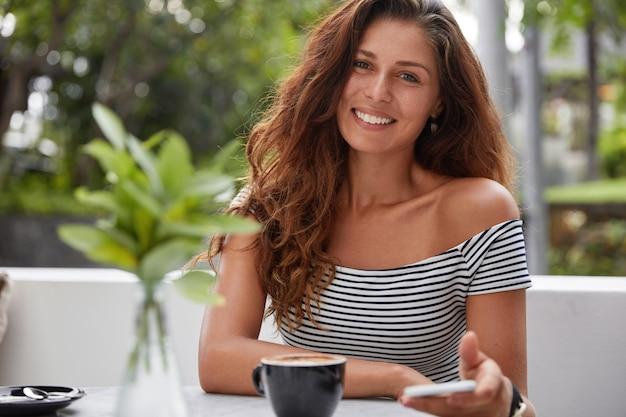 Donna felice che si siede in una caffetteria