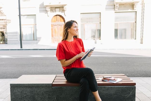 Donna felice che si siede sul banco con il diario