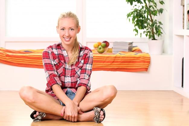 Donna felice che si siede sul pavimento