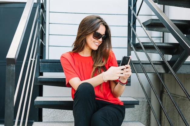 Donna felice che si siede sulla scala utilizzando il telefono cellulare