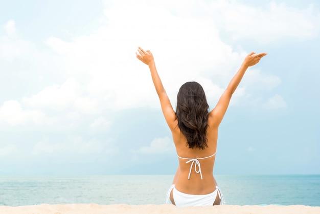 Donna felice che si siede sulla spiaggia in estate