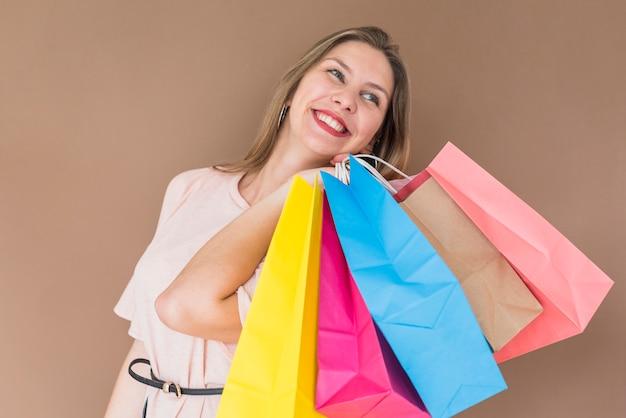 Donna felice che sta con i sacchetti della spesa variopinti