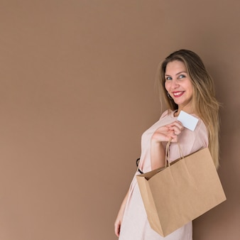 Donna felice che sta con il sacchetto della spesa e la carta di credito